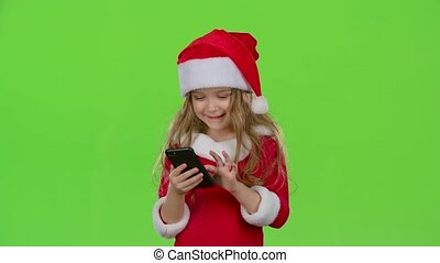 Child girl in an embrace photographed on a smartphone. Green...
