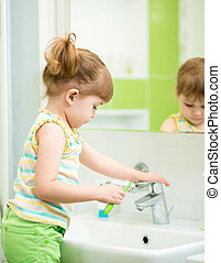Child girl in bathroom