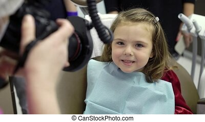 Child girl in dental clinic in dentist chair with doctor...