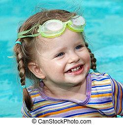 Child girl in goggles swimm pool.