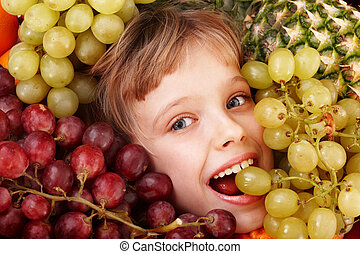 Child girl in group of fruit. Healthcare.