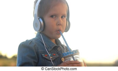 Child girl in headphones listens to music and drinking cocktail, juice, smoothies.