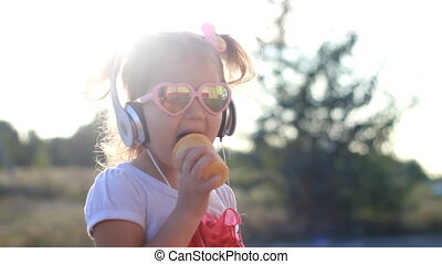 Child girl in headphones listens to music and eating ice cream.