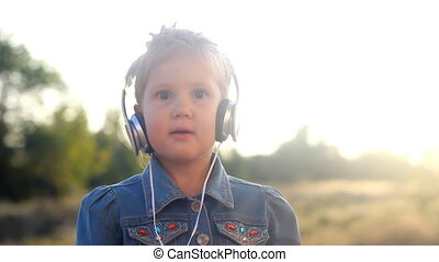 Child girl in headphones listens to music and rhythm. Portrait closeup baby at sunset on a summer day
