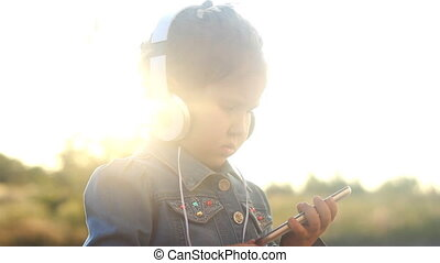 Child girl in headphones listens to music and rhythm to music from a mobile phone.