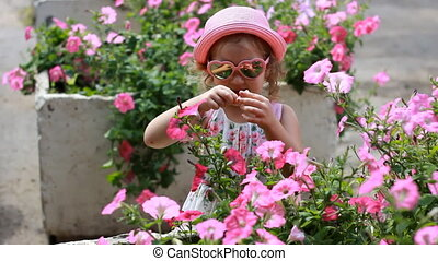 Child girl in pink glasses and a hat sniffs the aroma of...