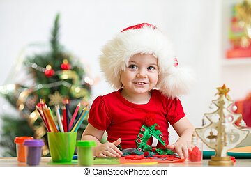 child girl in Santa hat making christmas decoration of plasticine