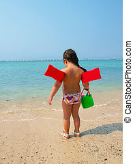 Child girl in summer on sea background