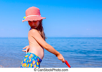 Child girl in summer straw hat is making poses with beach toys