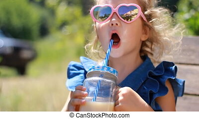 Child girl in sunglasses drinks smoothies in the park on a...