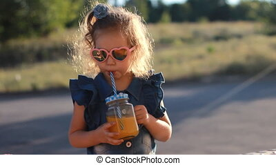 Child girl in sunglasses drinks smoothies in the rays of sunset on a summer day. Close up