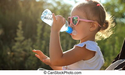 Child girl in sunglasses drinks water from a bottle. Portrait child close-up on a sunny day