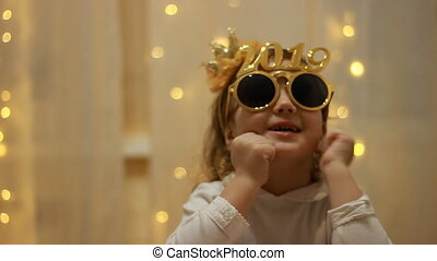 Child girl in sunglasses with the number 2019 is smiling and...