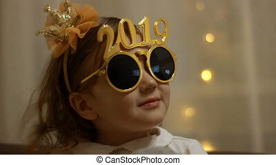 Child girl in sunglasses with the number 2019 smiles in the...