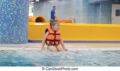 Child girl in the pool in the life jacket sits in the...