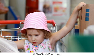 Child girl in the store chooses fruit. Grocery supermarket and shopping trolley