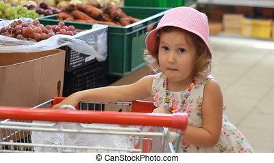 Child girl in the store chooses fruit. Grocery supermarket...