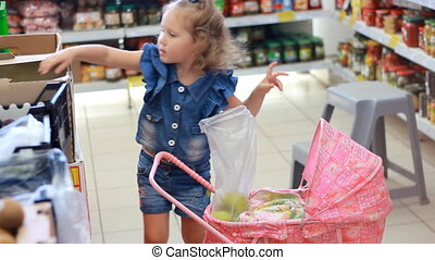 Child girl in the store makes purchases. Mother with child buys fruit.