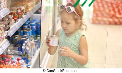 Child girl in the store opens the refrigerator door and buys baby food. Shopping in the supermarket