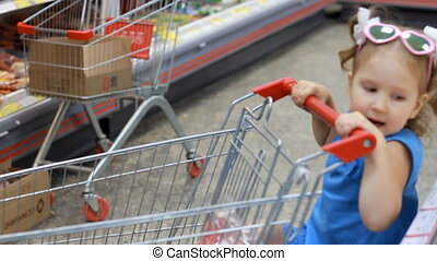 Child girl in the supermarket buys food with trolley for products. Baby shopping.