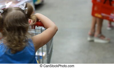 Child girl in the supermarket buys food with trolley for...
