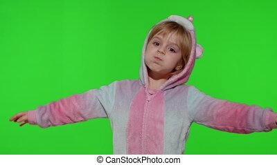 Child making silly funny faces, fooling around, showing tongue. Little teen kid girl in unicorn pajamas posing isolated on chroma key background. People emotions concept. Copy space. Slow motion