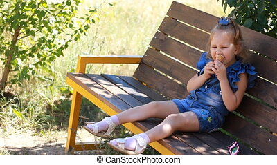 Child girl is eating ice cream while sitting on a bench in the park