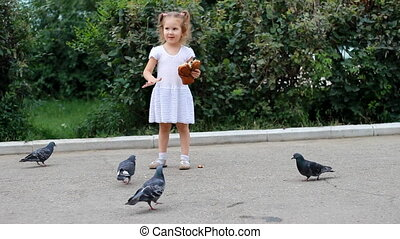 Child girl is feeding birds of pigeons and eats a loaf in the park.