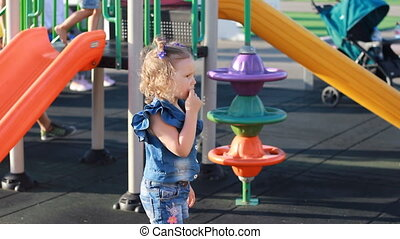 Child girl is lost in the playground and is looking for a...