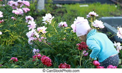 Child girl is plaing and dances in the garden with peonies....