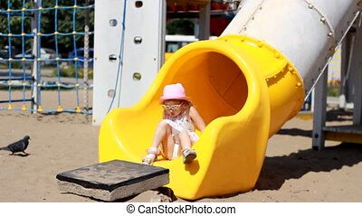 Child girl is playing on the playground. Attractions and...