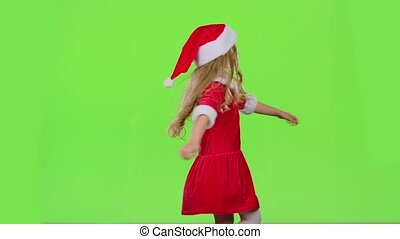 Child girl is spinning in her New Year's costume. Green screen