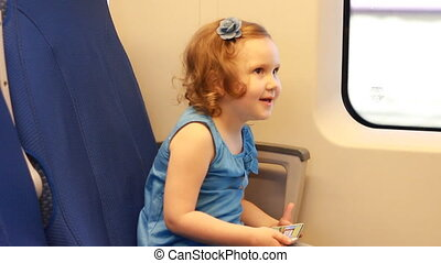Child girl is traveling by train. Baby rides on a...