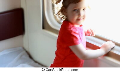 Child girl is traveling by train. Baby travels by rail and...
