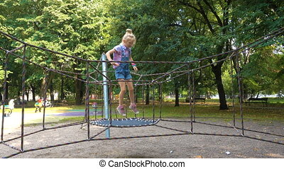 child girl jumping at the playground at the park