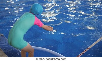 Child girl learns to dive in pool from standing position...