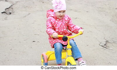 Child girl learns to ride a Bike