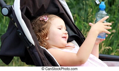 Child girl lies in a baby carriage and drinks water from a bottle. Thirst in summer.