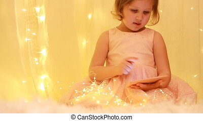 Child girl looking on the mobile phone screen and playing...