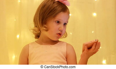Child girl looking on the smartphone screen and playing...