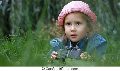 Child girl looking through binoculars and watching the...