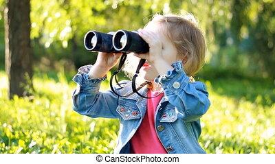 Child girl looking through binoculars and watching the nature