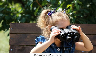 Child girl looking through binoculars and watching the...
