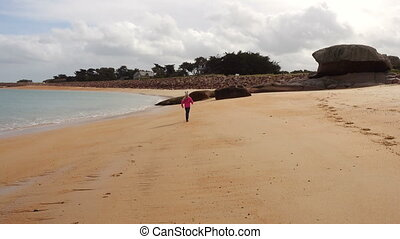 child girl on an empty beach - child girl walking and...
