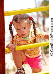 Child girl on ladder in playground.