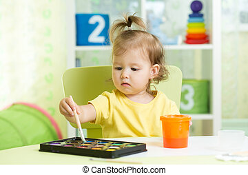 Child girl painting with watercolors at home or preschool nursery