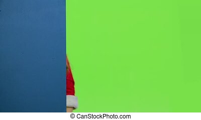 Child girl peeking out from behind the blue board. Green...