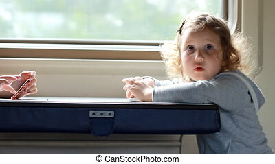 Child girl play in the game with smartphone in train. Baby playing game on the mobile phone in the road.