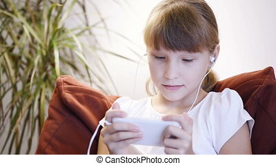 Child girl playing at smart phone - Child girl sitting on...
