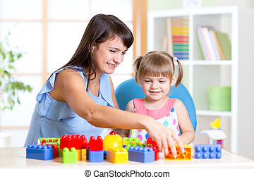 Child girl playing construction set with mother